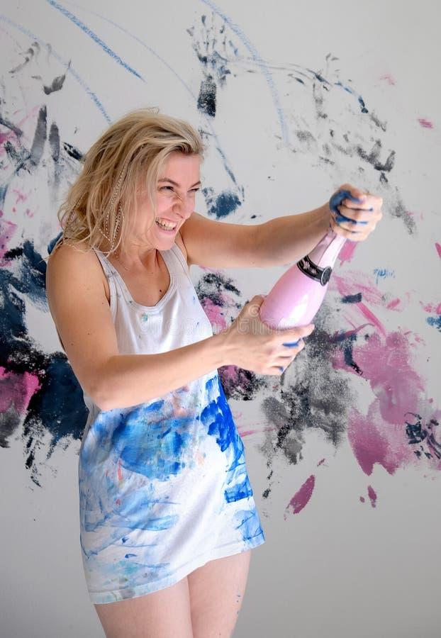 年轻女人艺术家打开一个闪耀的瓶在白色汗衫的香槟在前面o她的生日宴会的被绘的墙壁 库存图片