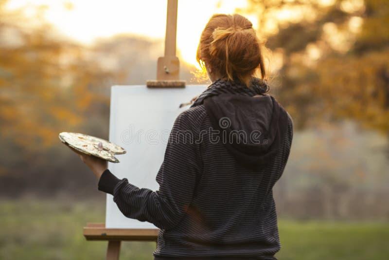 年轻女人艺术家本质上画在帆布的一张图片在一个画架本质上 免版税图库摄影