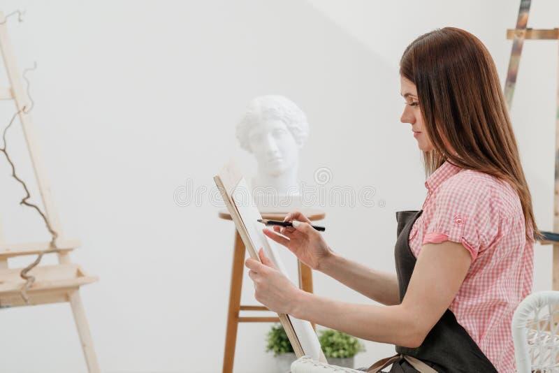年轻女人艺术家画在帆布的一支铅笔 图库摄影