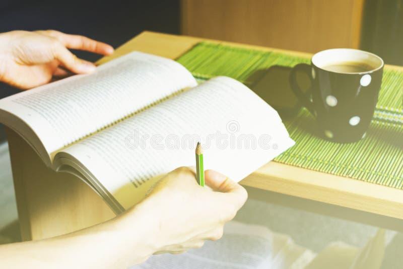 年轻女人藏品书和铅笔采取笔记和享用的用热的咖啡和手机在桌上 库存图片
