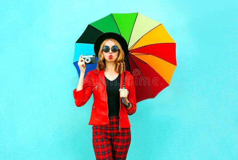 年轻女人藏品五颜六色的伞,拍在红色夹克,在蓝色墙壁上的黑帽会议的减速火箭的照相机照片 库存图片