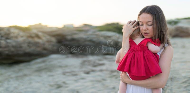年轻女人藏品户外可爱宝贝女孩在海滩,幸福家庭概念 库存照片