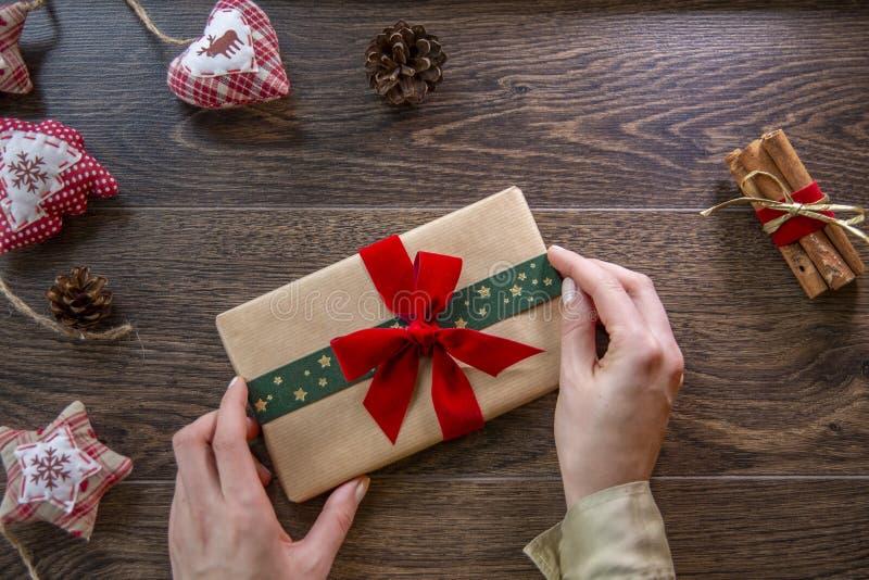 年轻女人藏品有红色和绿色丝带的礼物盒在木背景 免版税库存图片