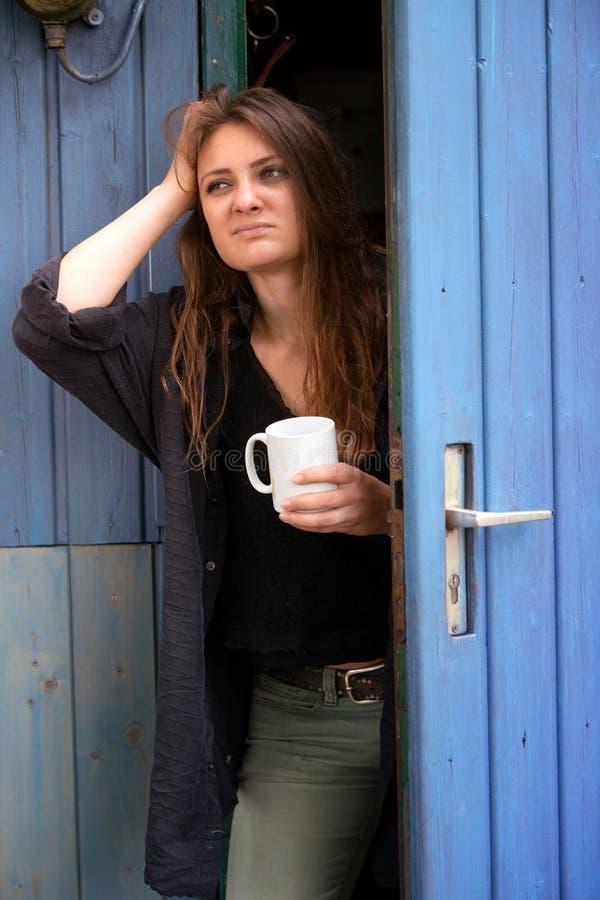 年轻女人藏品杯子和身分在看起来蓝色的门疲乏 免版税库存照片
