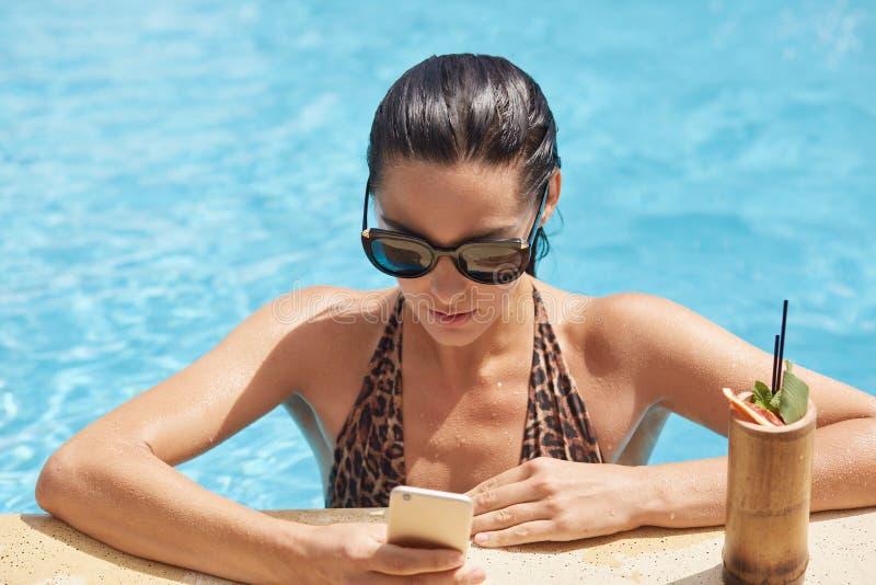 年轻女人藏品电话在手中和检查人脉,当喝鸡尾酒在游泳场时边缘  ?? 库存照片