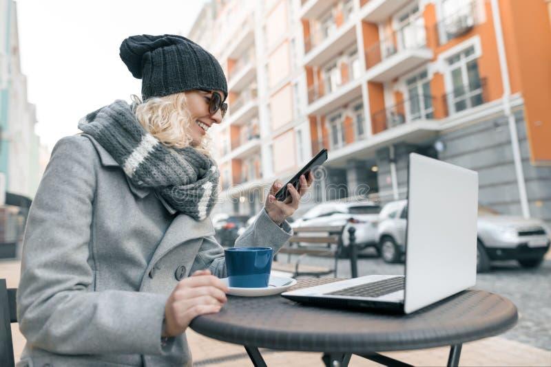 年轻女人衣服暖和帽子的博客作者自由职业者在与计算机膝上型计算机,手机的室外咖啡馆 都市的背景 免版税库存图片