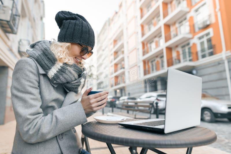 年轻女人衣服暖和帽子的博客作者自由职业者在与计算机膝上型计算机,手机,城市街道背景的室外咖啡馆 免版税库存照片