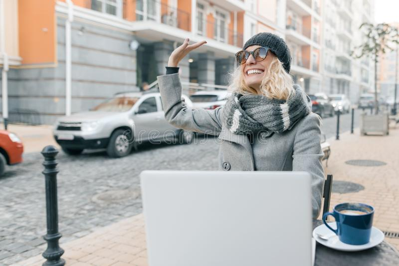 年轻女人衣服暖和帽子的博客作者自由职业者在与计算机膝上型计算机,手机,城市街道背景的室外咖啡馆 免版税库存图片