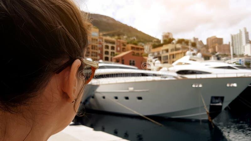 年轻女人观察在口岸,旅游放松的游艇在海边,特写镜头 库存图片