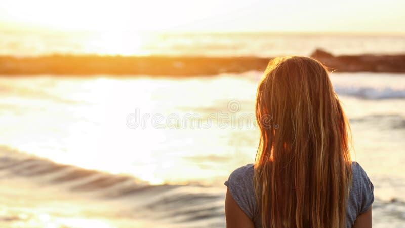 年轻女人观看在海的日落在海滩,从后面,在她的头发的细节,与空间的宽横幅的看法文本的 库存照片