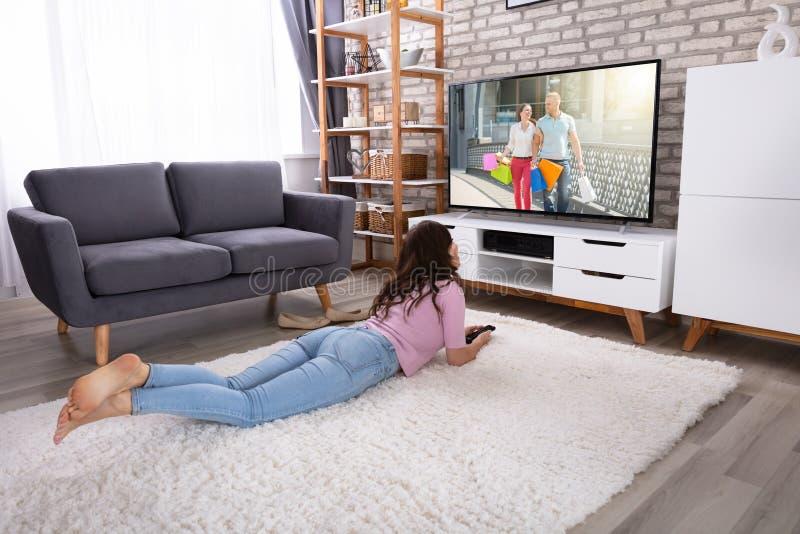 年轻女人观看的电视在家 免版税图库摄影