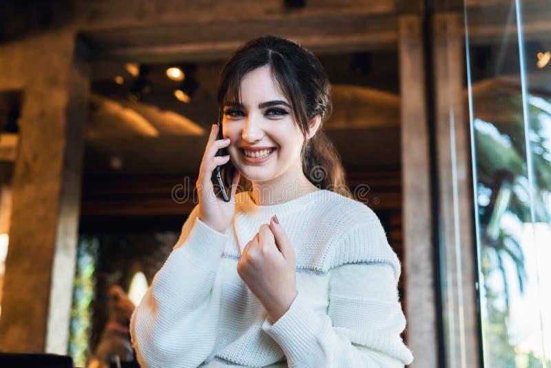 年轻女人谈话在手机,当单独坐在咖啡馆时 微笑的女孩有通话,当休息在咖啡馆时 免版税图库摄影