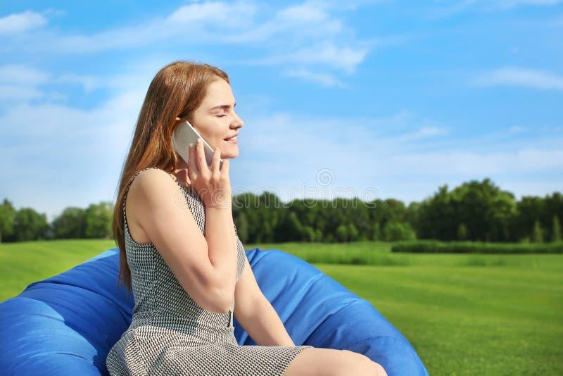 年轻女人谈话由手机,当坐辎重袋椅子户外时 库存图片
