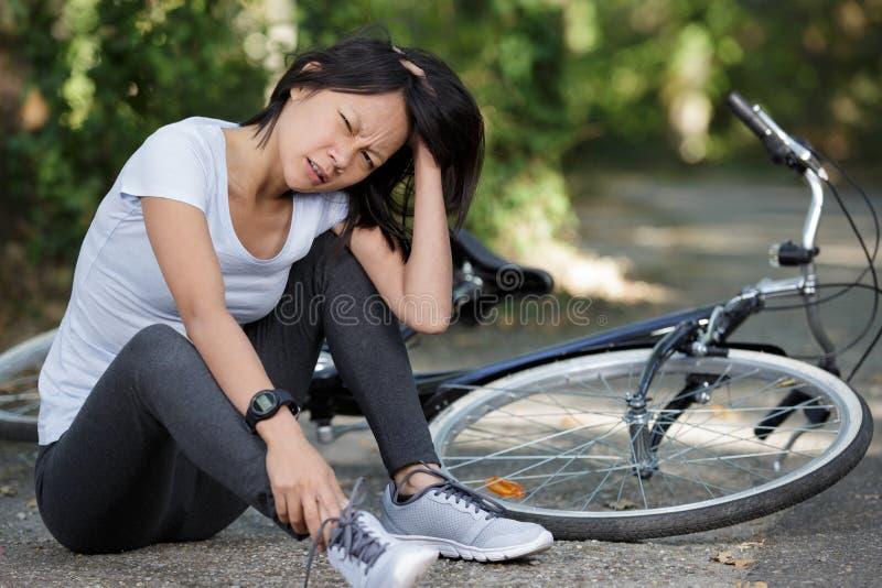 年轻女人跌下自行车在森林里 免版税库存图片