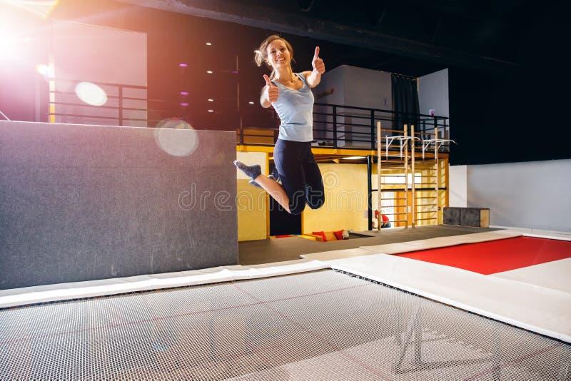 年轻女人跳跃在俱乐部绷床的运动员健身 免版税库存照片