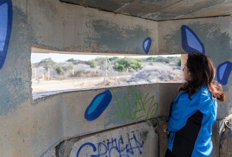 年轻女人通过在具体安全分离篱芭的发射孔看在以色列和黎巴嫩之间的边界 免版税图库摄影