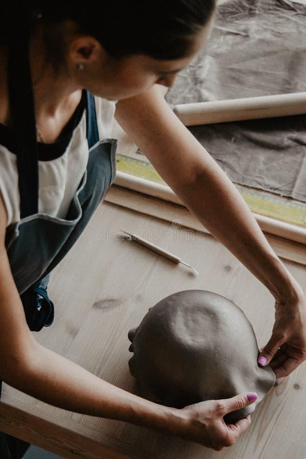 年轻女人铸造了从黏土的陶瓷板材 库存图片