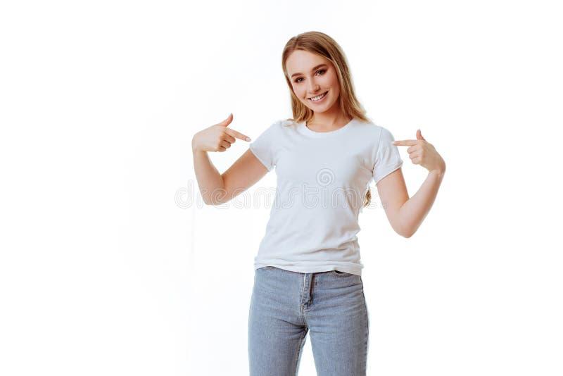 年轻女人陈列微笑,在偶然巧妙的衣物,被隔绝反对白色背景 库存照片