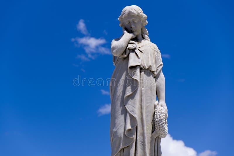 年轻女人雕象用在面颊的手 免版税库存照片
