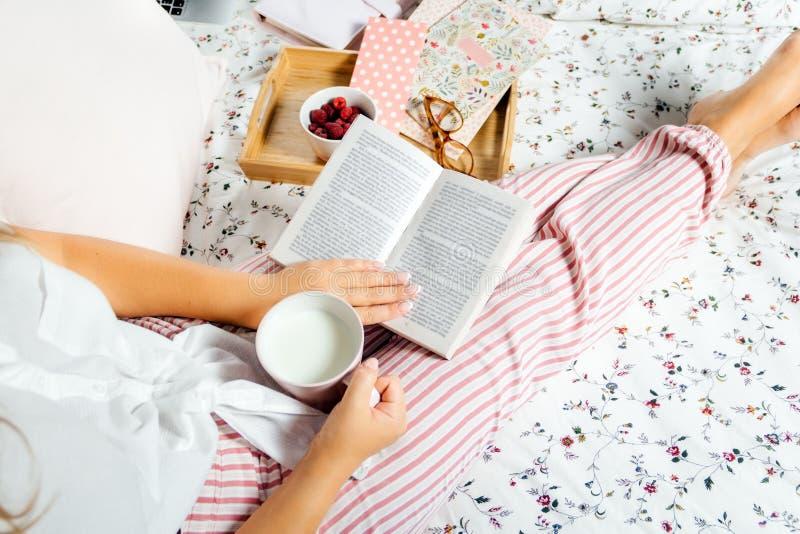 年轻女人饮用奶在家在床和看书,顶视图上 库存图片