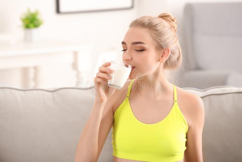 年轻女人饮用奶在家 饮食食物概念 免版税库存图片