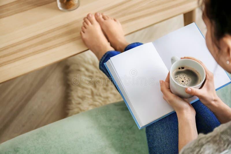 年轻女人饮用的咖啡一会儿看书在家 免版税库存图片