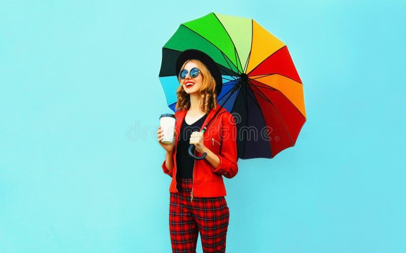 年轻女人饮用的咖啡和拿着走在红色夹克,在蓝色墙壁上的黑帽会议的五颜六色的伞 免版税库存图片