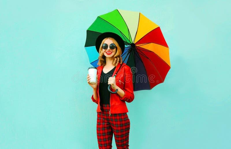 年轻女人饮用的咖啡和拿着走在红色夹克,在蓝色墙壁上的黑帽会议的五颜六色的伞 免版税库存照片