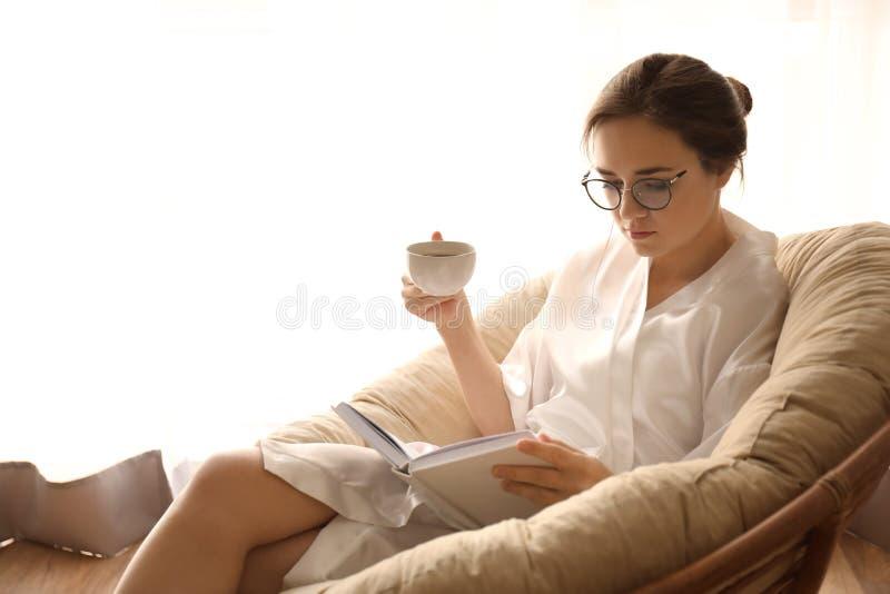 年轻女人饮用的咖啡,当在躺椅的看书在家时 库存照片