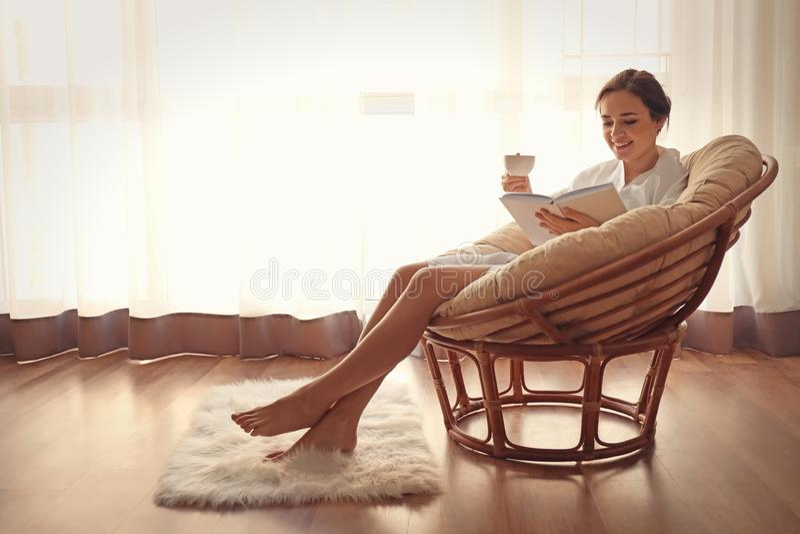 年轻女人饮用的咖啡,当在躺椅的看书在家时 免版税图库摄影
