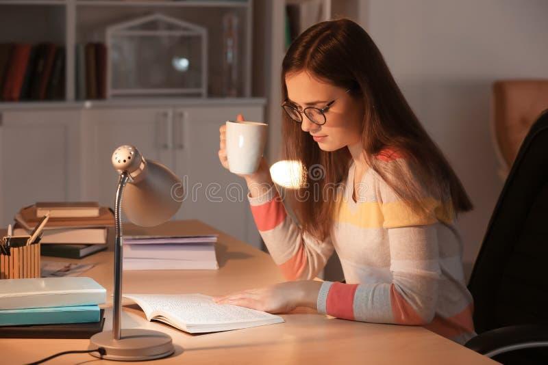 年轻女人饮用的咖啡,当看书在桌上在晚上时 库存图片