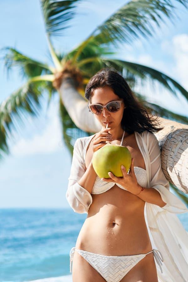 年轻女人饮用的椰子汁和放松在海滩在度假暑假 库存照片