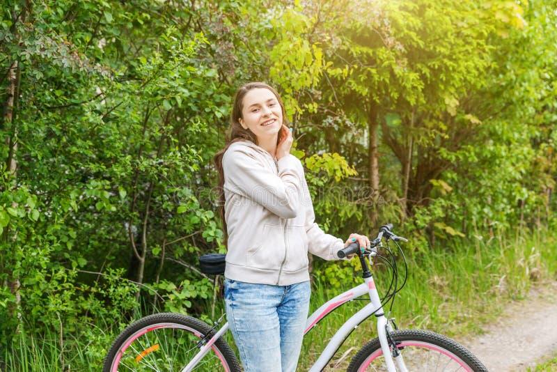 年轻女人骑马自行车在夏天户外城市公园 活跃人民 行家女孩放松和车手自行车 库存图片