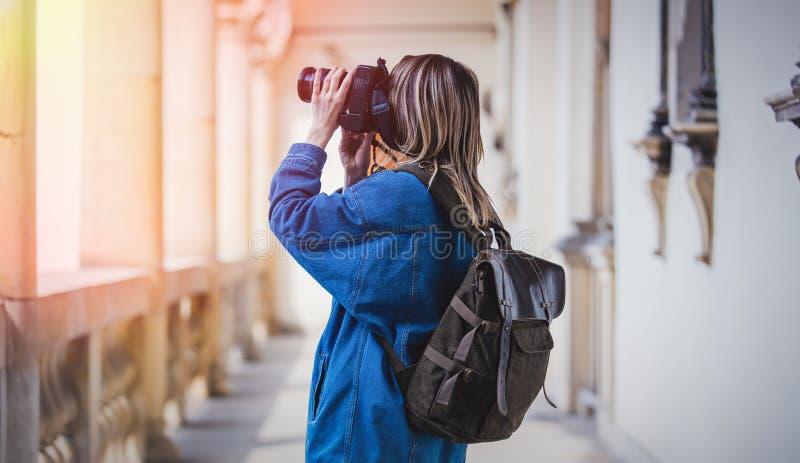 年轻女人,有照相机的专业摄影师在老城堡 库存照片