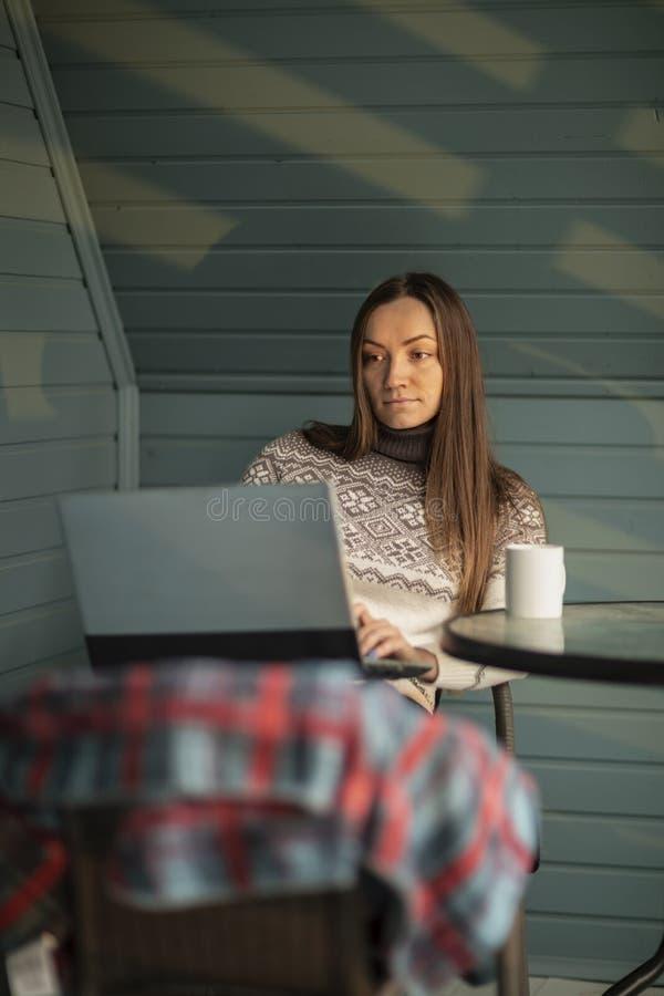 年轻女人,膝上型计算机,阳台,茶,自然 免版税库存图片
