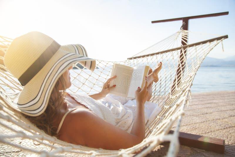 年轻女人,读在吊床的一本书在日落 免版税库存图片