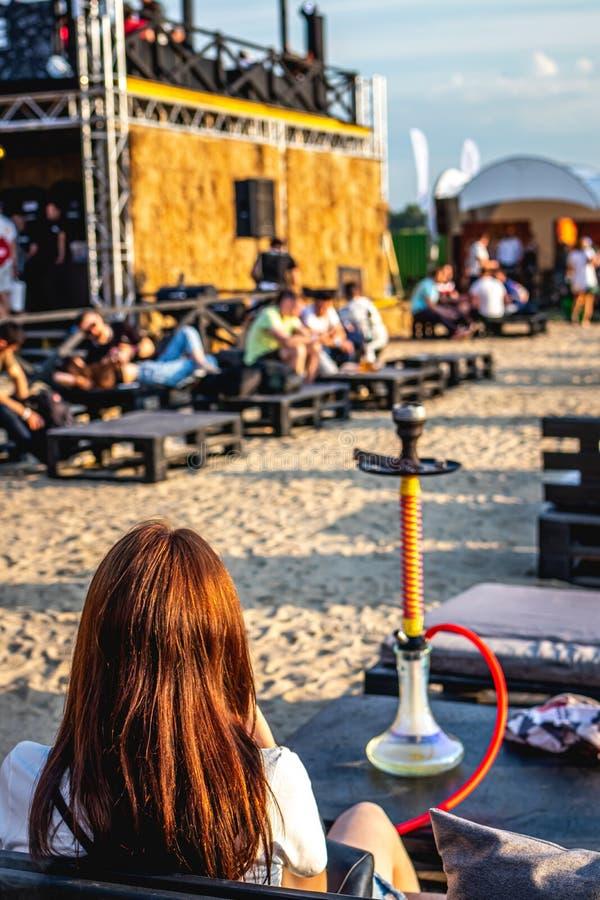 年轻女人vaping的户外 有水烟筒的妇女 免版税库存图片