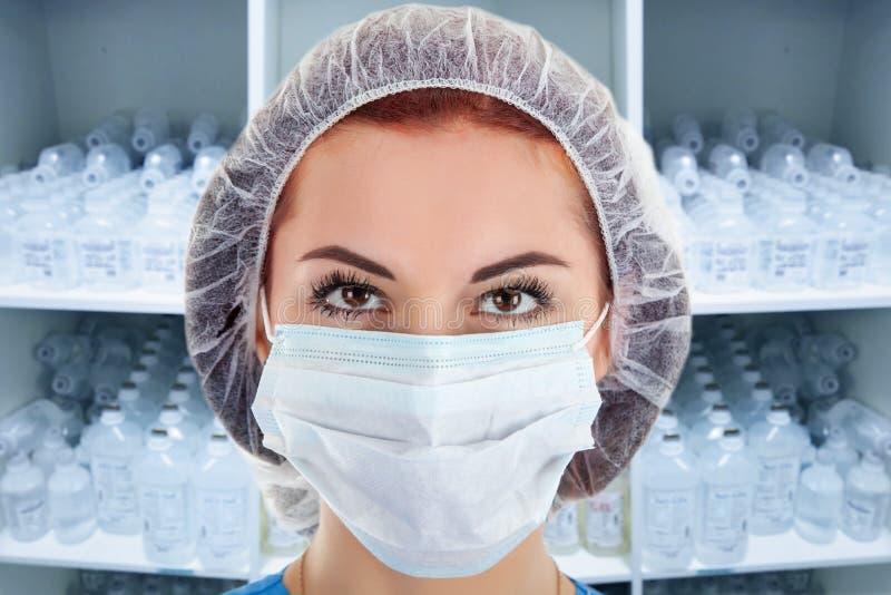 年轻女医生在橱柜里输液瓶 免版税库存照片