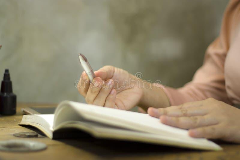 年轻女商人与笔一起使用在办公室,她超时停留 库存图片