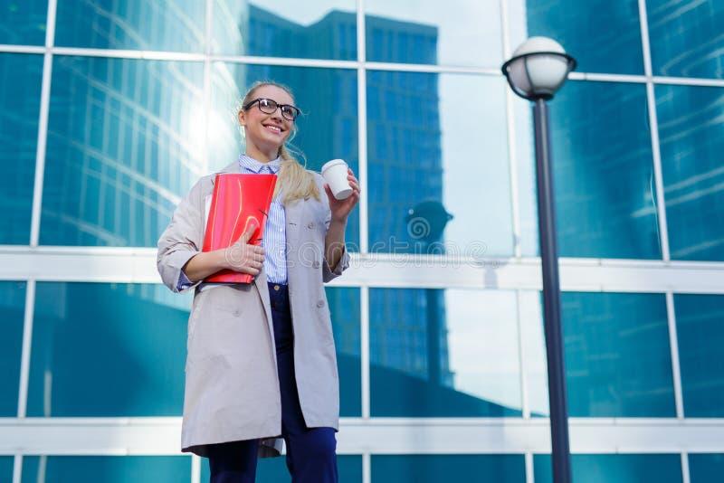 年轻女商人在她的与文件和咖啡的手文件夹举行 在事务旁边的女实业家身分 库存照片