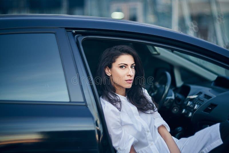 年轻女商人在汽车坐乘客座位 免版税库存照片