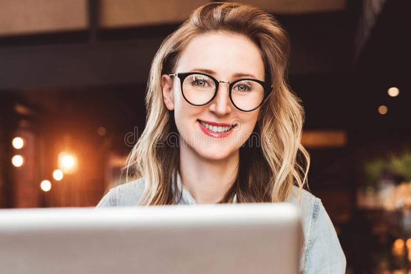 年轻女商人画象时髦玻璃的在咖啡馆,运作坐膝上型计算机 博客作者与追随者沟通 图库摄影