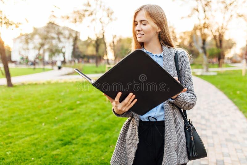 年轻女商人身分在有文件夹和lookin的一个公园 库存照片