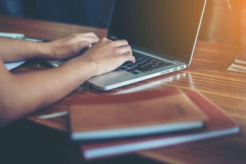 年轻女商人递键入在键盘对工作在办公室 图库摄影
