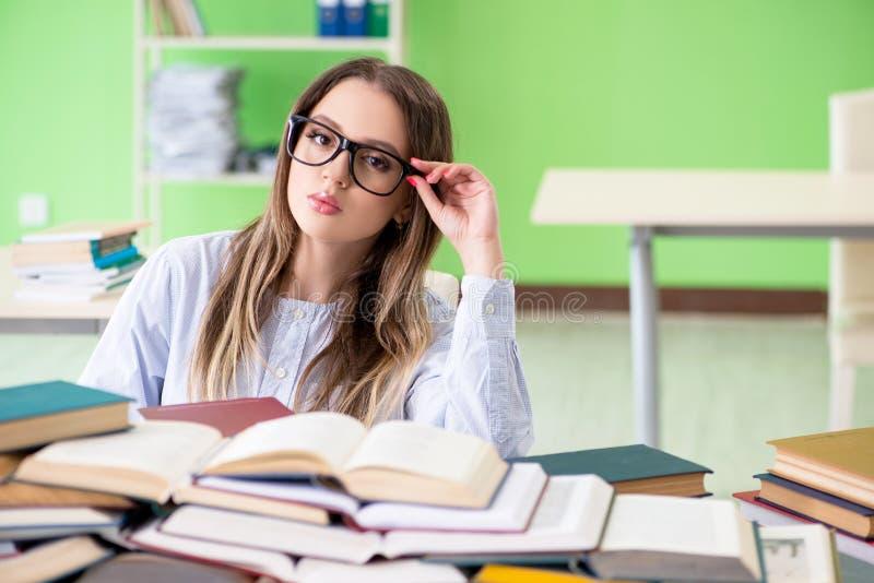 年轻女学生为与许多书的检查做准备 免版税图库摄影