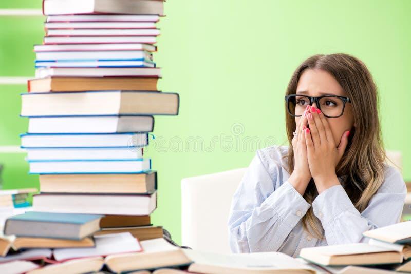 年轻女学生为与许多书的检查做准备 库存图片