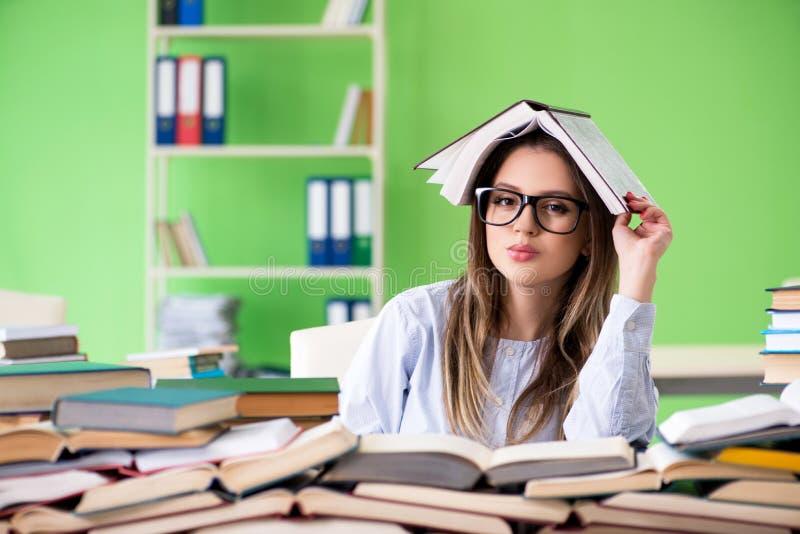 年轻女学生为与许多书的检查做准备 库存照片