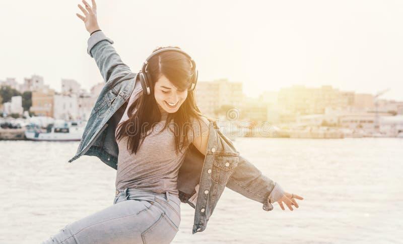 年轻女孩戴耳机听音乐 — 女人在户外与背景中的大海一起跳舞很有趣 — 温暖对比滤镜 库存图片