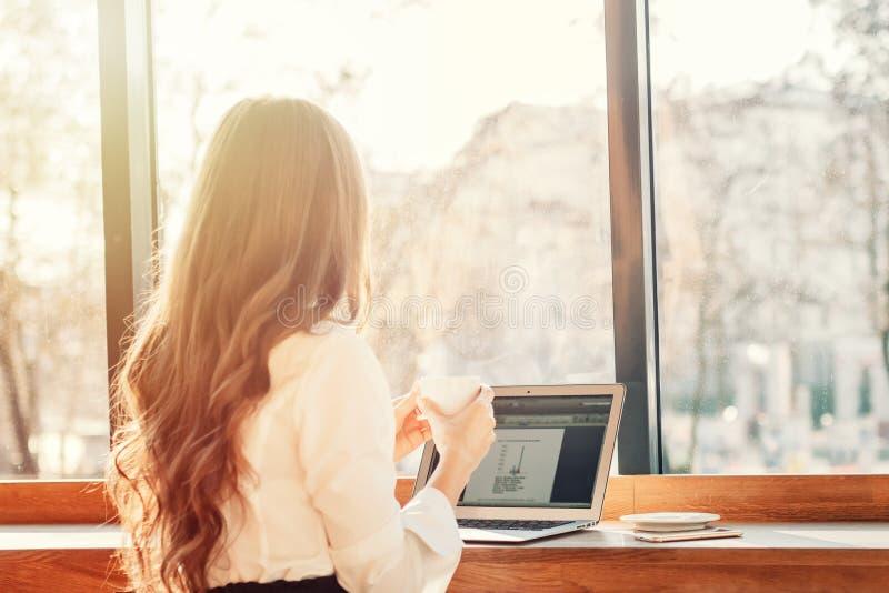 年轻女实业家喝咖啡在咖啡馆靠近窗口 妇女工作使用膝上型计算机 库存图片