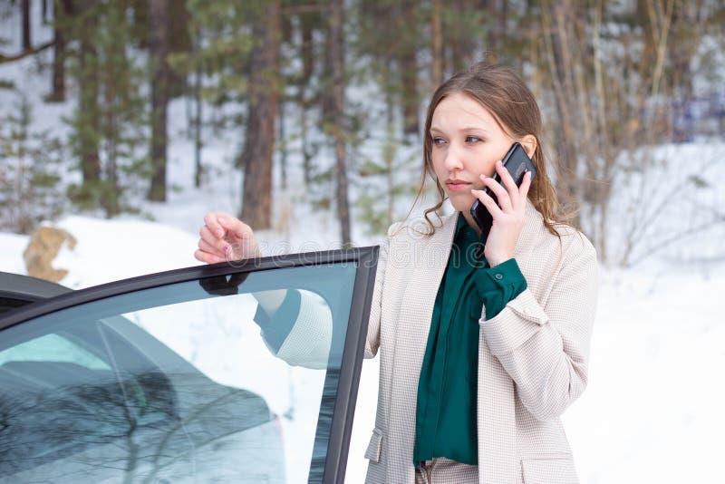 年轻女实业家在电话里说在她的汽车外面 库存照片